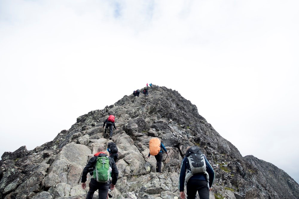 Several people climb the rocky peak